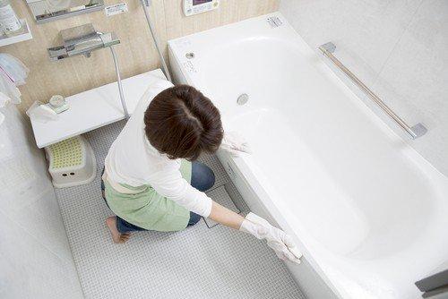 A woman scrubs her bathtub to make it gleam like new again