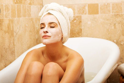 A woman sits int he bathtub with a moisturizing face mask on