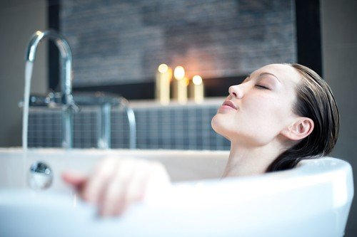 A woman meditates in the bath