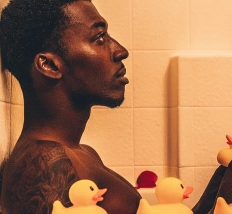 man with rubber duckies in bathtub