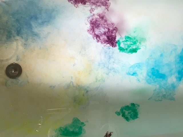 different colored soap dyes in bathwater look like a watercolor