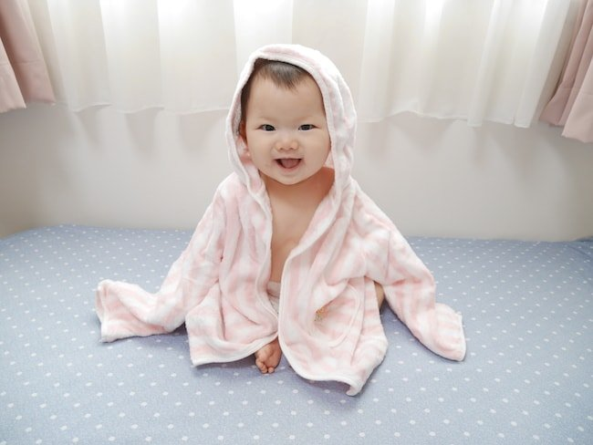 After visiting the Japanese bath house, a baby gets warm in a bathrobe