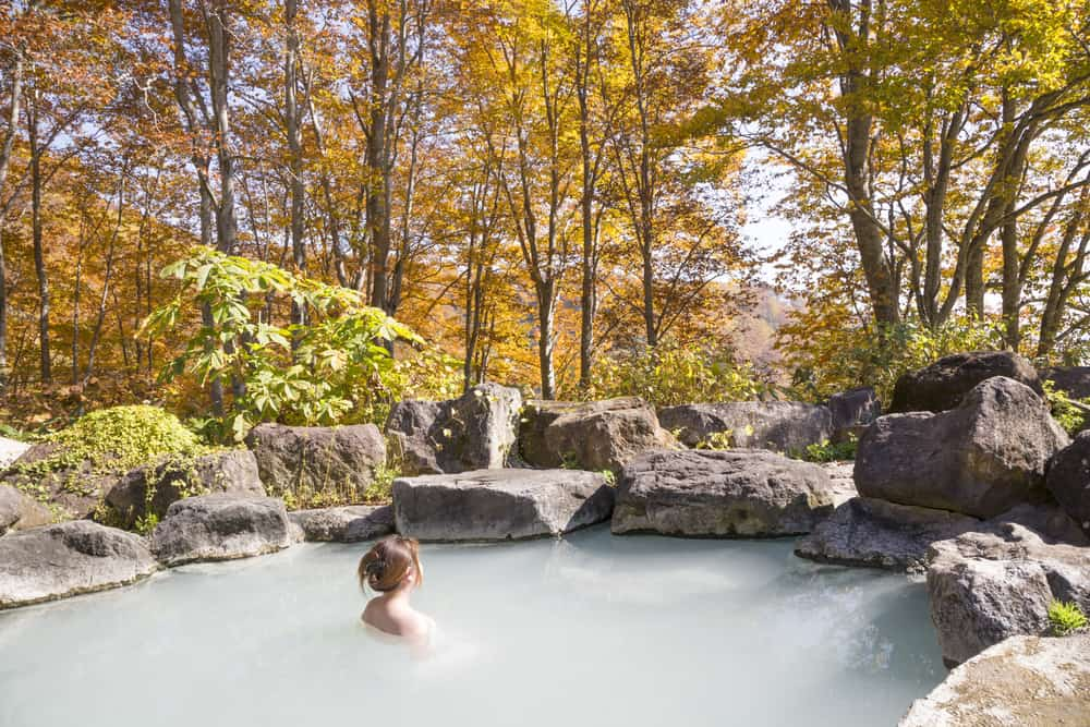 woman bathes in onsen in autumn