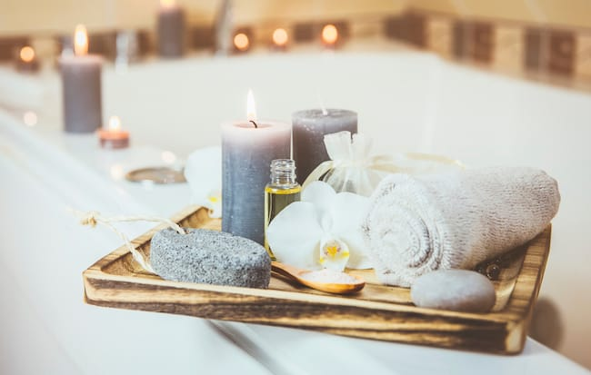 bathtub with candles and towel on ledge