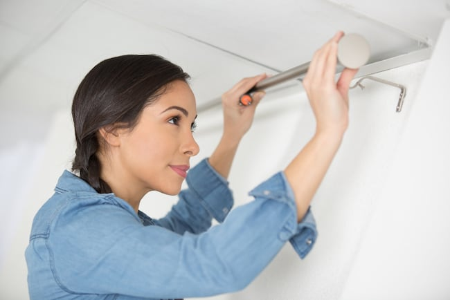 Woman hangs rod during DIY bathroom renovation