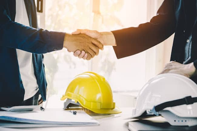 Two men shake hands across a desk. A yellow construction hat is on the table beneath them.