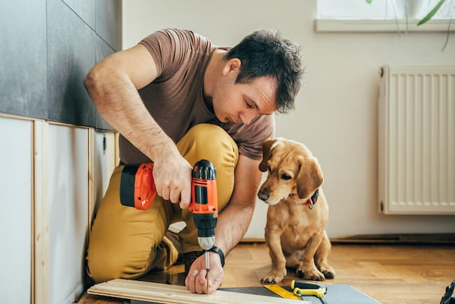 A man works on bathroom remodel while his puppy looks on