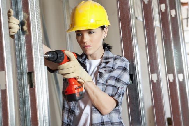A subcontractor drills holes during a bathroom remodel