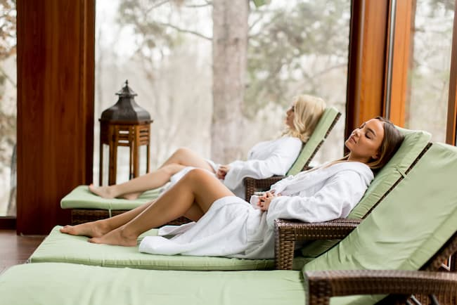 Two women relax on lounge chairs before entering float tanks