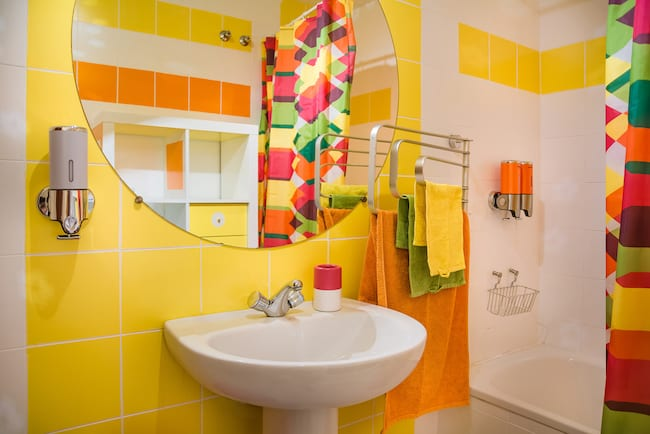 A bathroom with bright yellow and orange color scheme