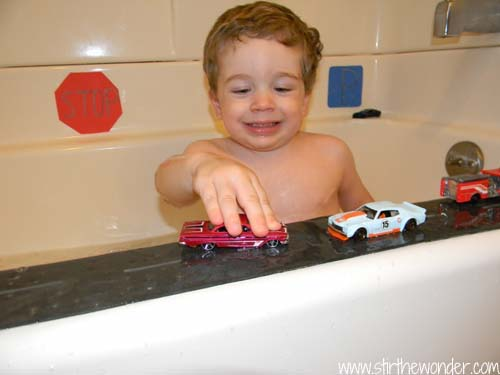 A preschooler plays with cars on the ledge of the bathtub