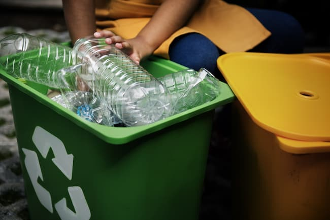 Children pick plastic bottles out of a recycle bin to use for a bath activity