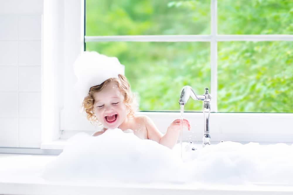 child in bath by window