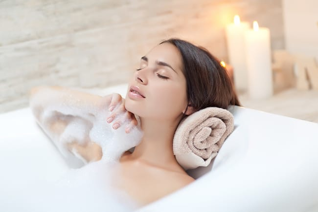 woman in bathtub with towel rolled up behind her neck