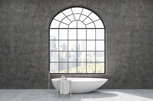 freestanding bathtub under giant window