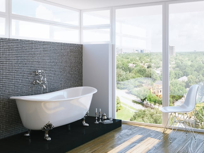 a clawfoot tub with a view out floor to ceiling windows of a rolling hillside
