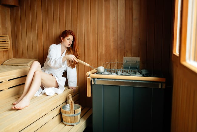 A woman creates steam in Finnish sauna by pouring water on hot stones