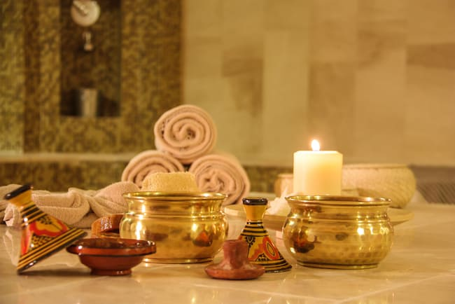 gold bowl, lit candle, rolled towels