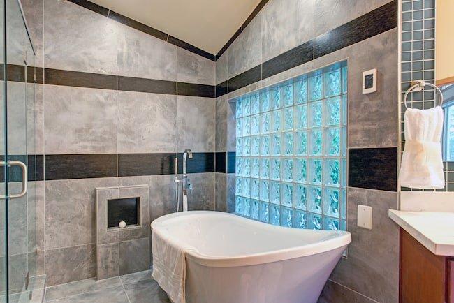 glass brick wall by freestanding tub
