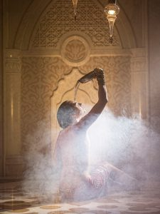 A bather sits in the steam of the hammam and pours water on her head
