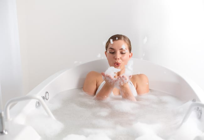 woman in freestanding tub blowing bubbles