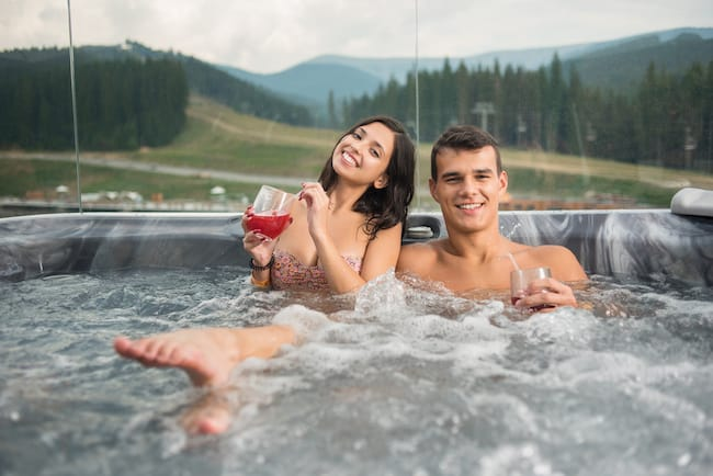 A young man and woman smile in the hot tub