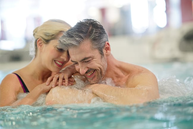 a couple snuggles in a hot tub