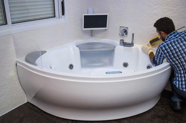 a man installs a jacuzzi tub