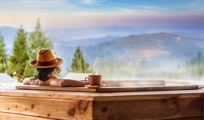 a woman sits in an outdoor hot tub and looks across the mountains