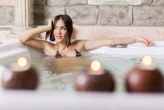 young woman relaxing in hot tub with candles lit
