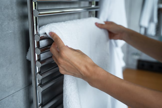 a person puts a white towel over the rails of a towel radiator