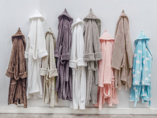 9 bathrobes of different colors hanging on hooks