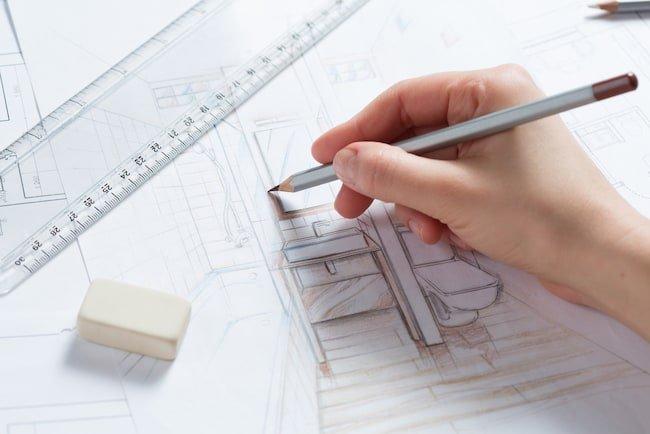 a hand draws a blueprint of bathroom