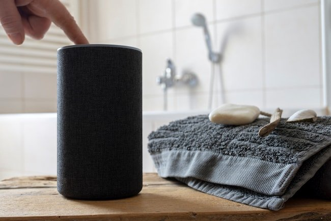 A finger turns on a waterproof speaker that sits on the bathroom vanity counter