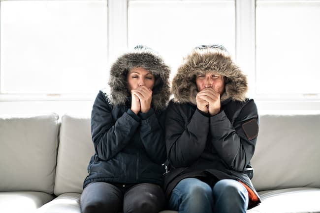man and woman sit on their couch wearing winter coats in a freezing cold house