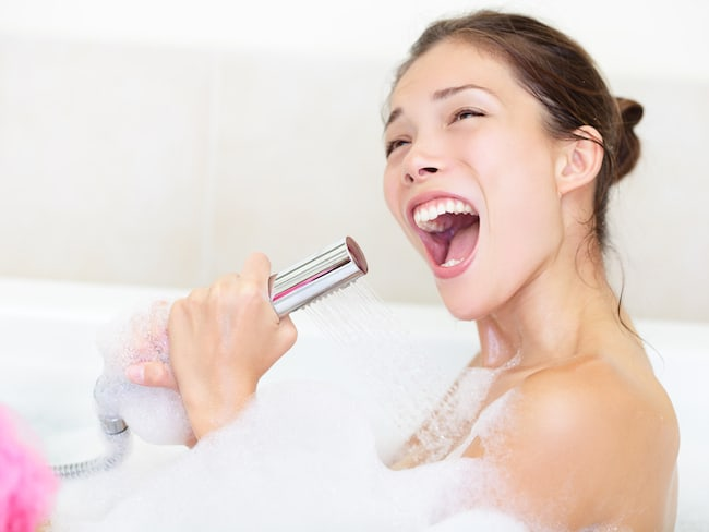 a woman sings in the bathtub and uses the shower sprayer as a microphone