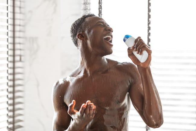 man singing into shampoo bottle in bathroom