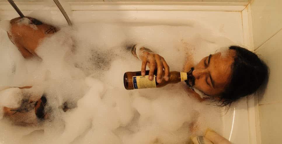 man in bubble bath drinking beer