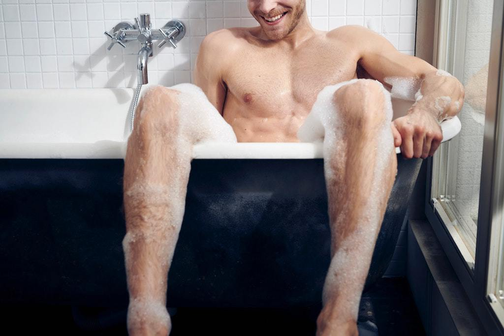 man in blue clawfoot tub with legs hanging over the side of the bathtub