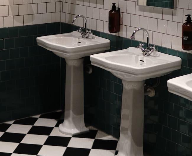 two pedestal sinks on black and white tile floor