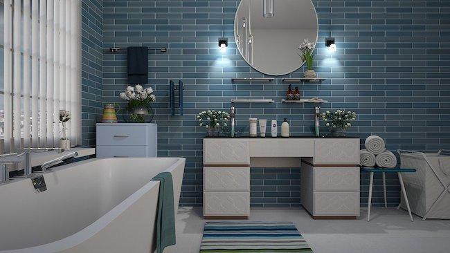 round bathroom mirror above modern vanity with tub