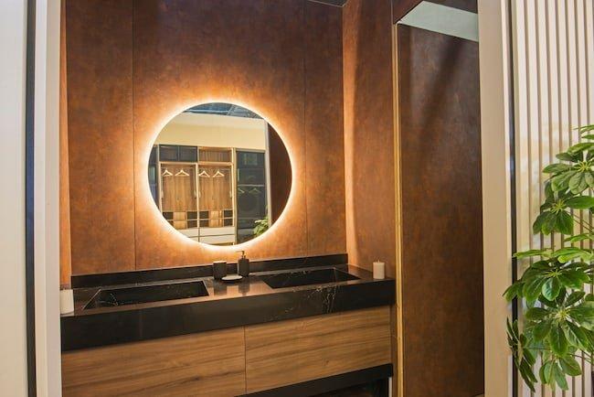 Zen bathroom with led light strip around perimeter of round vanity mirror