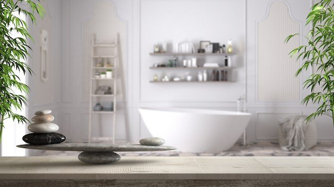 white zen bathroom with stone sculpture and plants