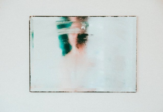 a woman looks in a fogged up bathroom mirror