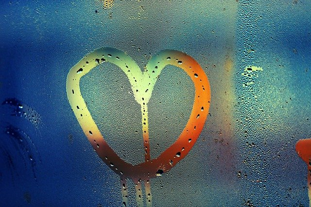 steamed up bathroom mirror with condensation and a heart shape made with someone's finger