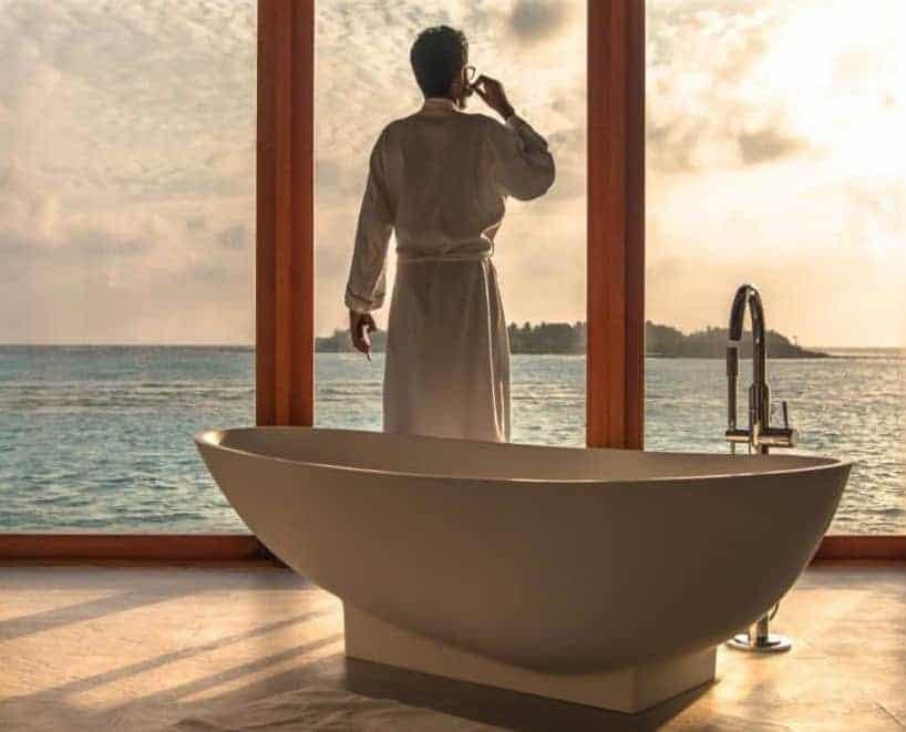 a man in bathrobe looks out window to ocean, a freestanding tub behind him