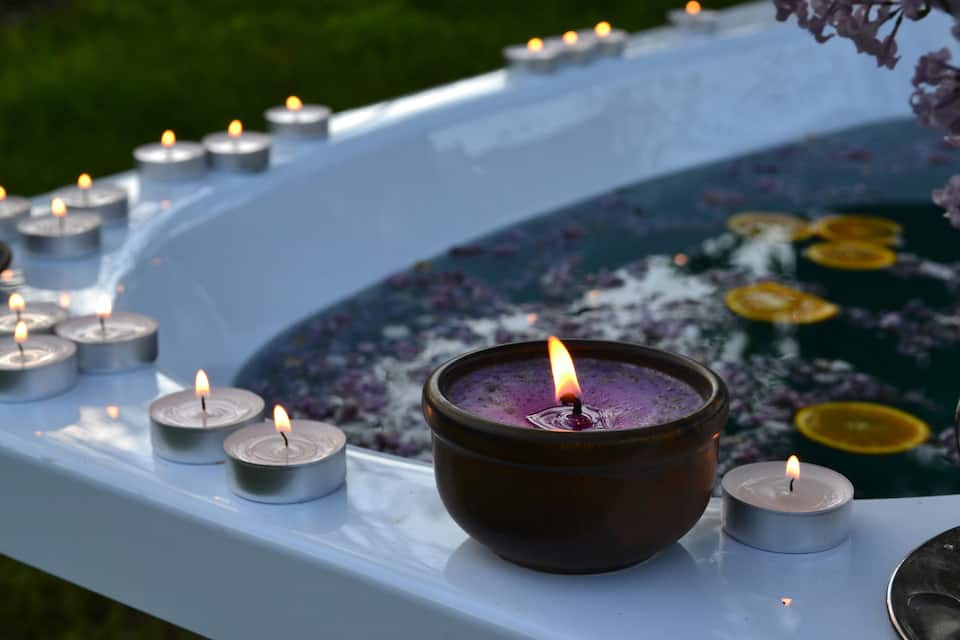 bathtub with candle and flower petals on ledge