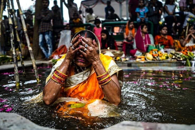 A Hindu woman in colorful dress bathes in the river